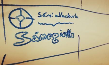 Govva whiteboard tavvalis mas sárgojuvvon Sámi allaskuvla namma, logo ja sátni Sámegiella.